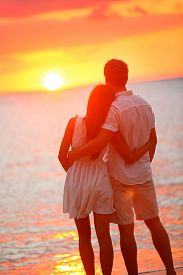 picture of couple  - Honeymoon couple romantic in love at beach sunset - JPG