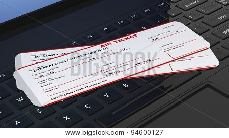 Two air tickets on black laptop keyboard