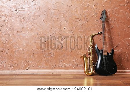 Electric guitar and saxophone on brown wall background