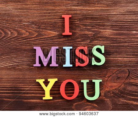 Inscription I MISS YOU made of colorful letters on wooden background
