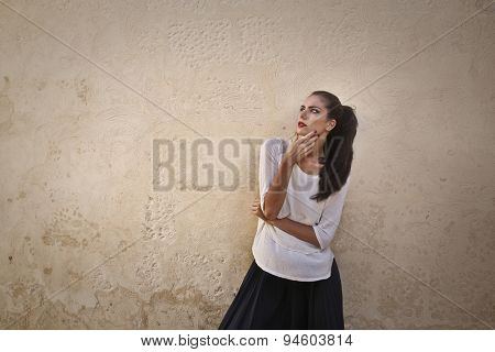 Beautiful girl wearing red lipstick standing against a wall