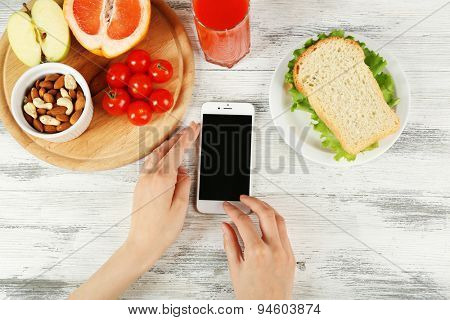 Food and mobile phone in female hands on wooden background