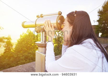 young woman tourist watching at the beautiful landscape from the telescope