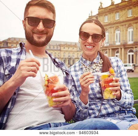 urban photo of smiley couple with fruits