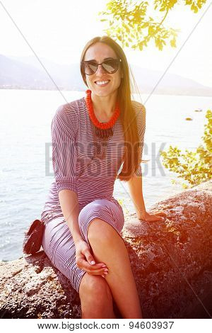 beautiful woman sitting against beautiful landscape and smiling