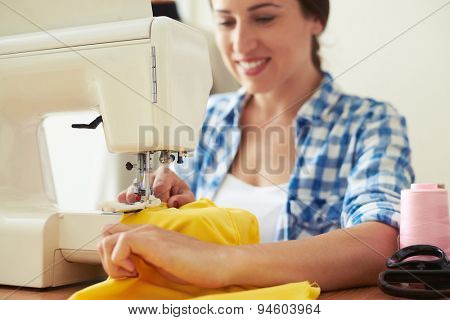 seamstress sewing yellow dress. focus on sewing-machine