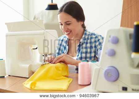 young woman working on sewing machine and smiling