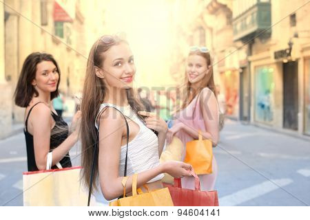 Three young girls doing shopping in the city