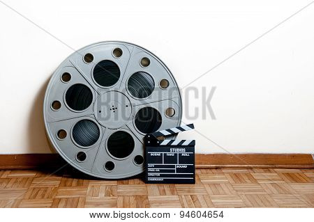 Cinema Movie Roll With Clapper On Wooden Floor