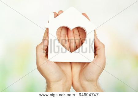 Female hands holding house on light blurred background