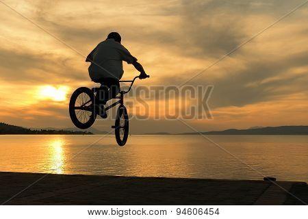 Beautiful sunset and biker's tricks.