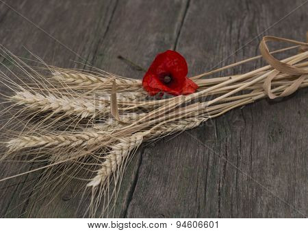 The Linking Of Wheat Decorated With A Flower Of Red Poppy