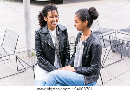 Two north African teen friends sitting together whispering
