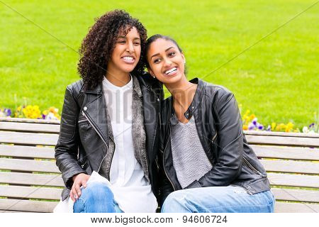 Two north African teen friends sitting together on park bench talking