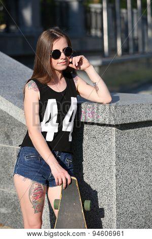 Beautiful tattooed girl with skateboard, outdoors