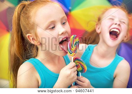 Happy twin sisters with many colorful umbrellas