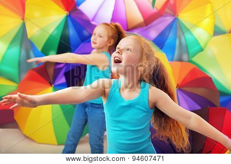 Twin sisters playing with colorful umbrellas