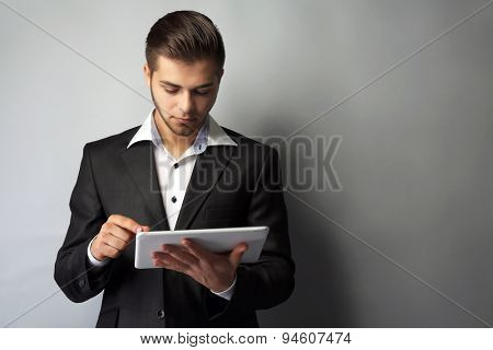 Handsome businessman holding tablet on gray background