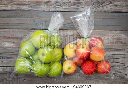 Apple fruit in plastic bag on wood table