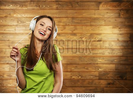 Young woman with headphones on wooden background