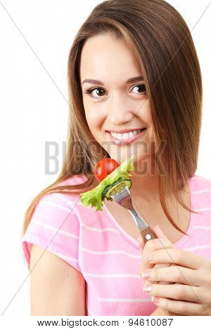 Healthy young woman with vegetables on fork isolated on white