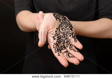 Closeup image of henna on female hand on dark background