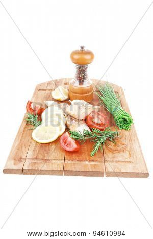 savory fish portion : grilled norwegian salmon fillet with green chinese onion, red cherry tomatoes , allspice pepper in grinder, rosemary twigs and lemon slice on wooden board over white background