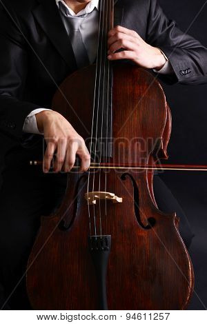 Man playing on cello close up