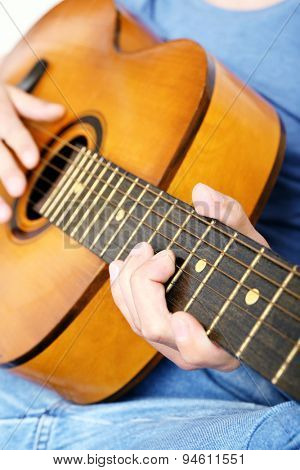 Young man playing on acoustic guitar close up