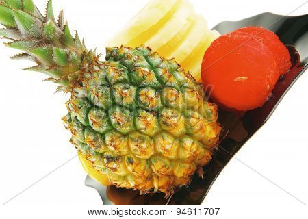 raw pinapple on black plate isolated over white background