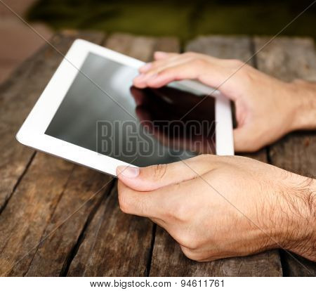 Hands holding digital tablet on wooden table background