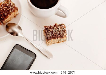 Coffee Cup With Biscuits And Smartphone On White Table Top View
