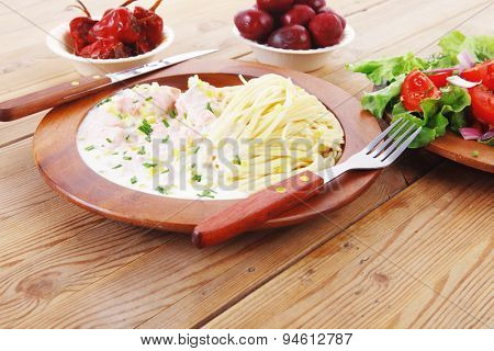 mediterranean cuisine: fresh rose wild salmon baked in cream cheese sauce with italian pasta and red hot pepper on wooden dish over table with vegetable salad