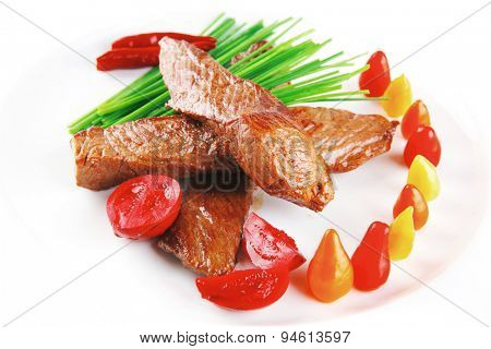 hot fresh grilled red beef meat fillet with vegetables  green chives and peppers on china plate isolated over white background