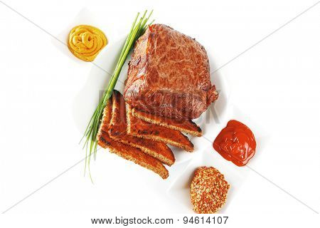 served beef meat fillet mignon with spices and toasted bread isolated on white background