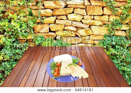 savory set of cheese greek goat feta yellow fromage french on blue plate over wooden table at outdoor garden near old ancient wall