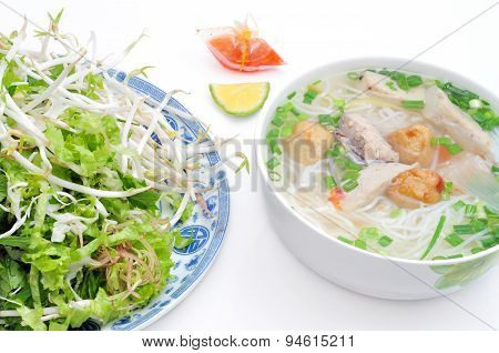 Bun cha ca or Vietnamese rice vermicelli with grilled fish and herbs on a white background