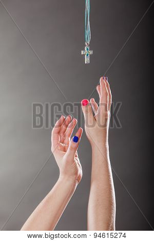 Closeup Of Human Hands Reaching Cross Necklace