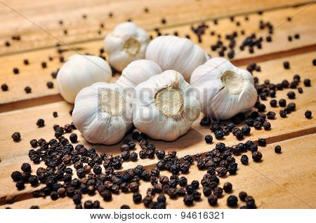 Garlic and pepper on a wooden background