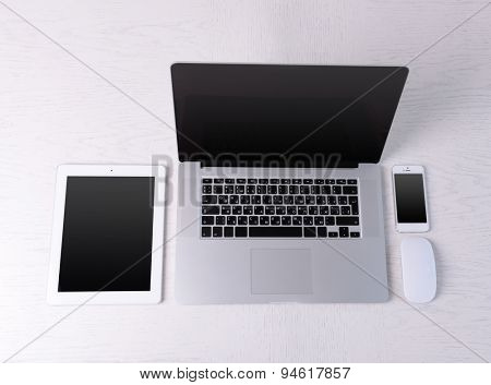 Laptop, mouse, tablet and mobile phone on white table, top view