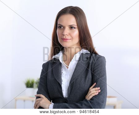 Portrait of businesswoman standing with crossed arms in office