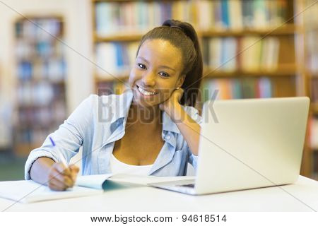 pretty female african college student using laptop in library