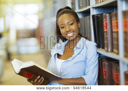 happy female african american college student in library