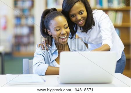 cheerful african american college girls using laptop computer