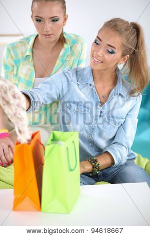 Two young women sitting with laptop  and credit cart