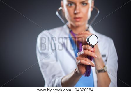 A female doctor with a stethoscope listening, isolated on grey background
