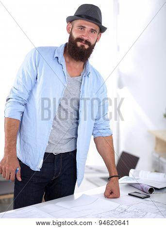 Portrait of male designer with blueprints at desk in office.