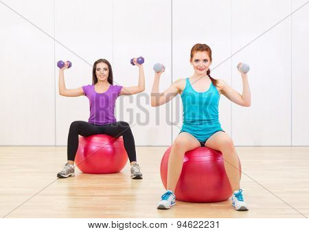Two sporty young girls at fitness club