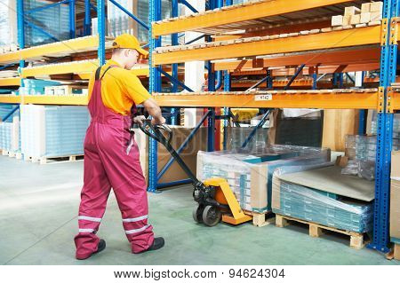 male worker in warehouse working with hand forklift