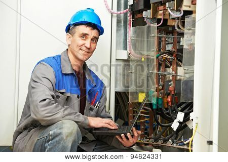 electrician engineer inspector with computer near the fuse box